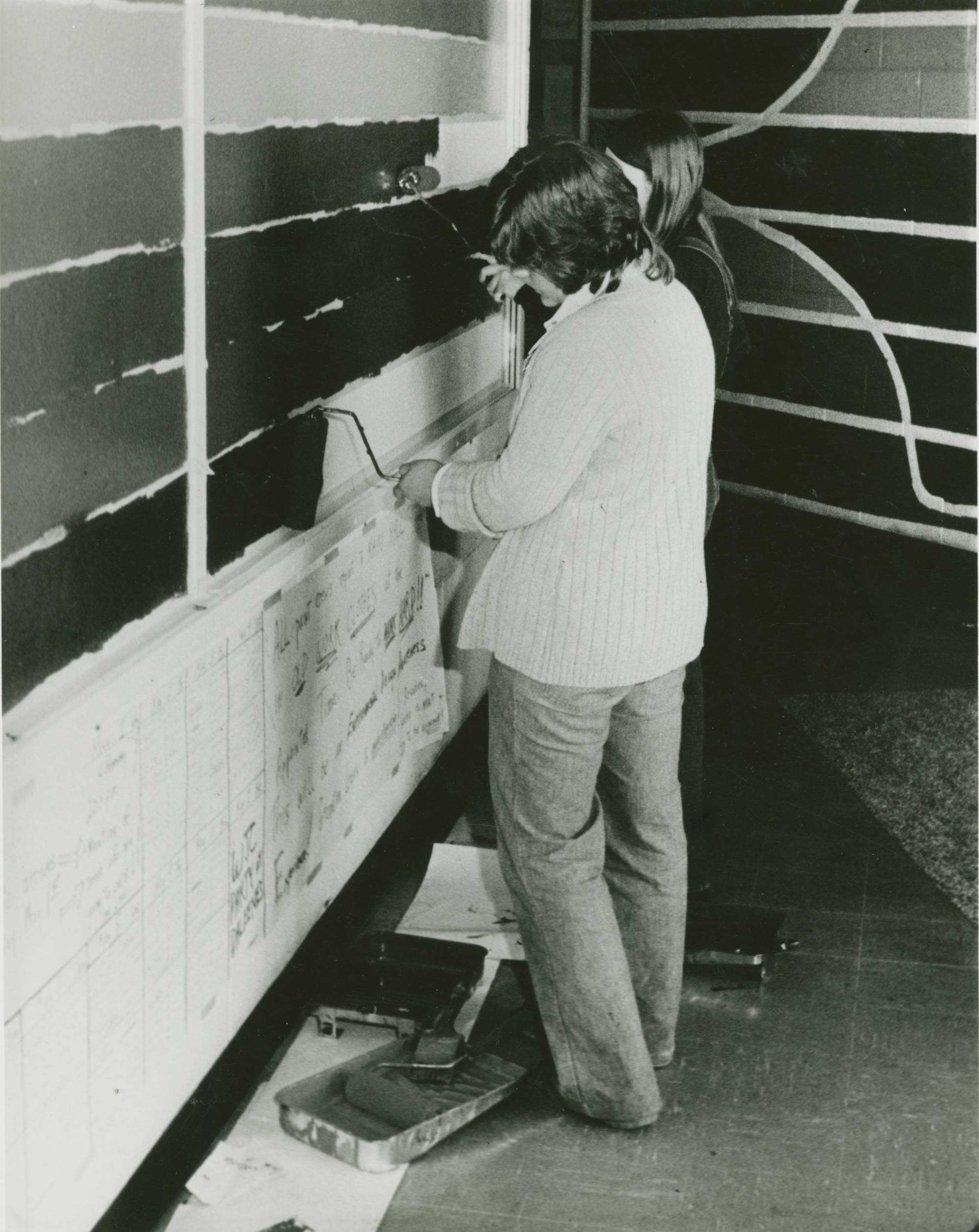 A black and white photo of a student painting a mural in Lake Superior Hall.